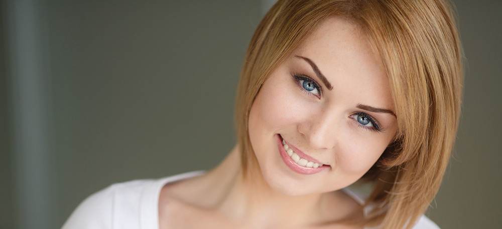 A beautiful portrait of a fair-haired young woman with beautiful hair,grey eyes,sweet smile and beautiful eyebrows,dressed in a white t-shirt with a deep neckline,isolated on a gray background.